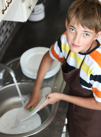 homemaking: boy doing the dishes in the kitchen