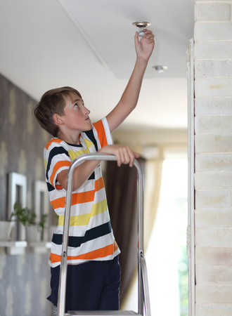 Boy on a ladder replaces a light bulb Stock Photo