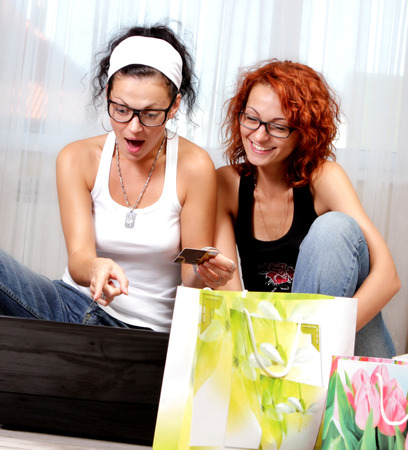 Two pretty beatiful girls shopping over internet