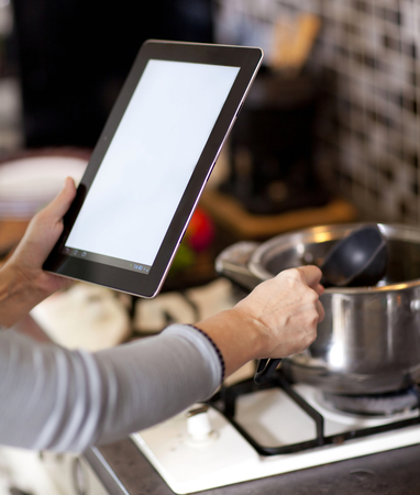 female hands holding a laptop at the dining table in the kitchen