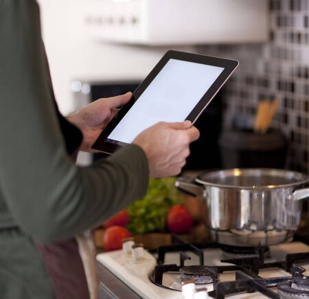 male hands holding a laptop at the dining table in the kitchen Stock Photo
