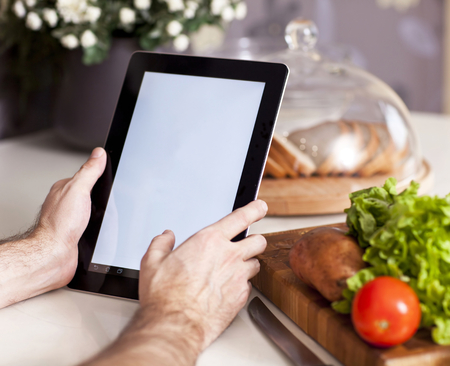 male hands holding a laptop at the dining table in the kitchen Imagens