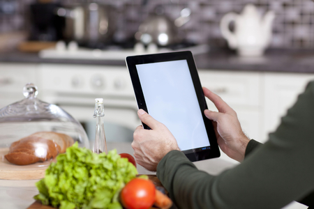 male hands holding a laptop at the dining table in the kitchen Standard-Bild