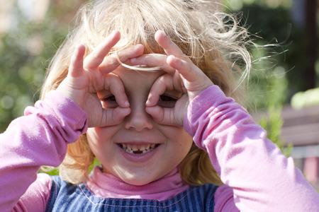 Beautiful little blonde girl, has happy fun cheerful smiling face Standard-Bild