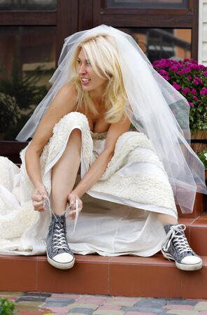 humor: Beautiful smiling bride sitting on the porch and putting on old blue trainers
