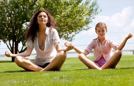 Young beatiful Mother and daughter meditating together