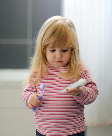 hygeine: A little girl brushing her teeth at bathroom