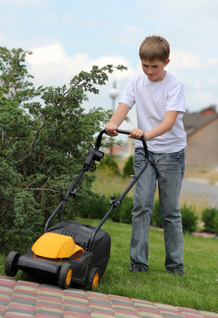 mows: Teen boy mows the lawn mower electric