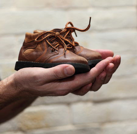 nostalgy: Dirty hands holding a pair of old childrens shoes