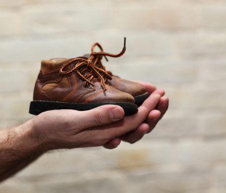 manos sucias: Dirty hands holding a pair of old childrens shoes