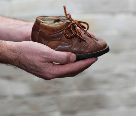 manos: Dirty hands holding a pair of old childrens shoes