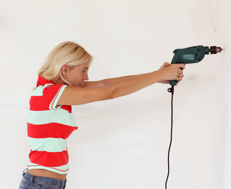 tinkering: A young woman drilled a hole in a wall Stock Photo