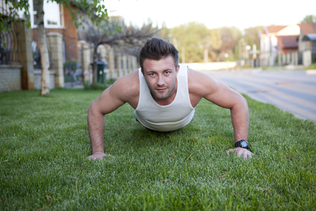 Push ups sport fitness man doing push-ups. Male athlete exercising push up outside in sunny sunshine. Fit shirtless male fitness model in crossfit exercise outdoors. Healthy lifestyle concept