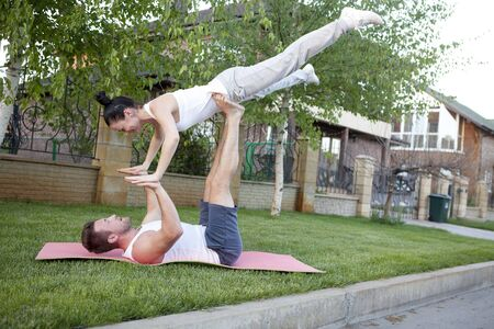 tantra: An attractive man and woman practice tantra yoga on a grass before the house Stock Photo