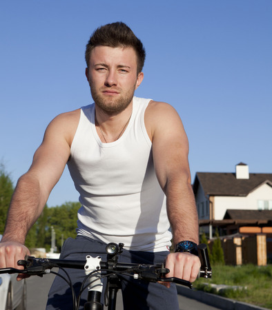 stubbly: Portrait of happy, stubbly, caucasian, casual man on bicycle outdoor, leaning against fence.