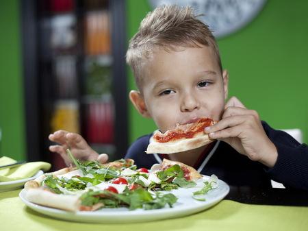 child eating pizza in restaurant