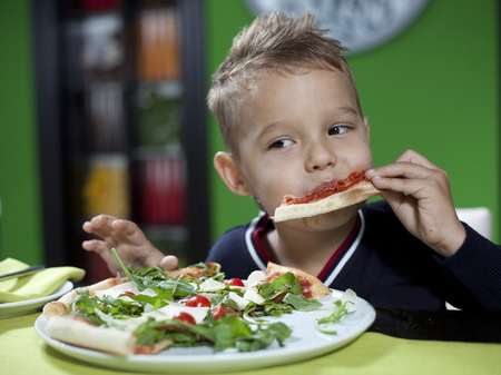 child eating pizza in restaurant