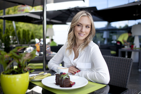 young stylish woman sitting in cafe, enjoying healthy food, city street, boho outfit, europe vacation, fashion Stock Photo