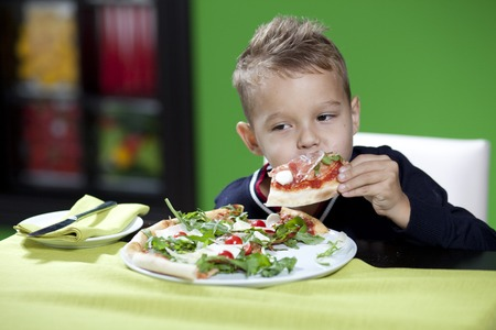 only boys: child eating pizza in restaurant