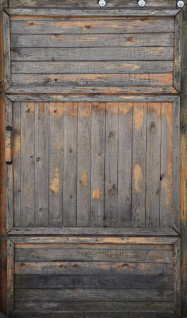 Old wooden door gate. Paint peels off and rotting of the boards begins.