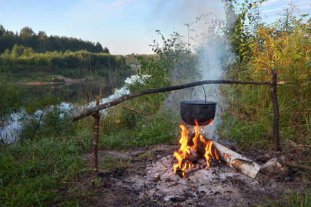 A pot of tea is boiling on a fire in the depths of the autumn forest.