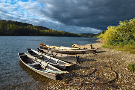 Old wooden boats on the banks of the Vishera River. Ural mountains in Russia Archivio Fotografico