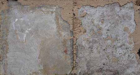 An old concrete surface with traces of destruction exposed stones interspersed 写真素材