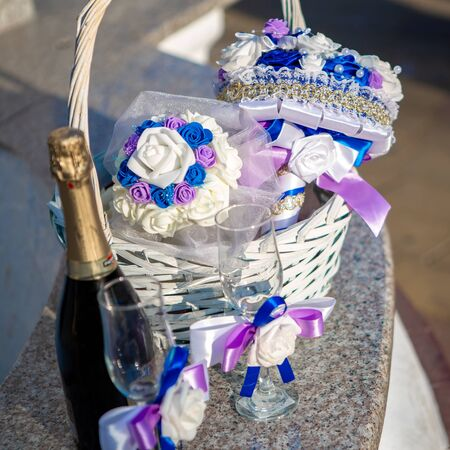Wedding arrangement. Bridal bouquet. Bridal bouquet in a basket with a bottle of champagne and glasses. Wedding design concept. Wedding composition