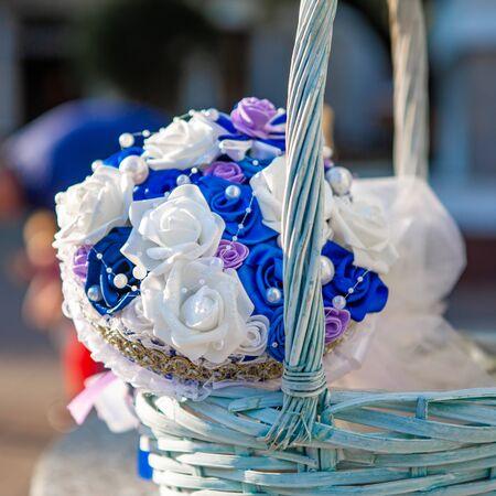 Wedding arrangement. Bridal bouquet. Bridal bouquet in a white wicker basket. Focus on the bouquet. Wedding design concept. Wedding composition. White with blue.