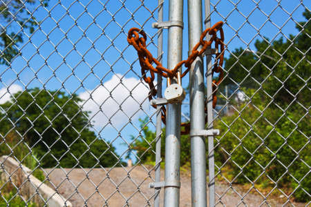 A chain link fence locked with a rusty chain and a padlock