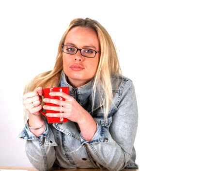 Blond Woman holding a hot beverage looking into the camera