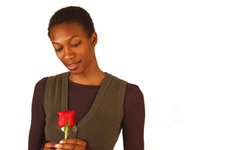 African America woman holding and looking at a single red rose