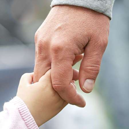 Closeup of a child and parent holding hands