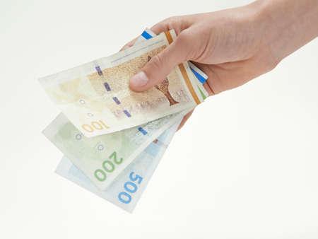 デンマークの通貨を持っている手のクローズ アップ