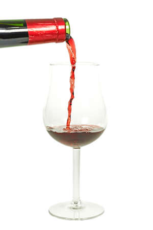 intense flavor: Pouring red wine into a glass isolated on white