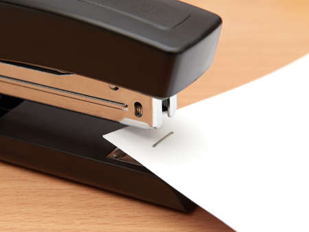 office stapler: Closeup of a modern office stapler joining paper sheets Stock Photo