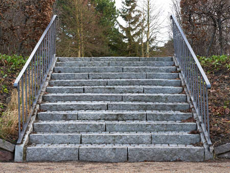 rise to the top: Grey stone stairway with iron bars in the sides Stock Photo