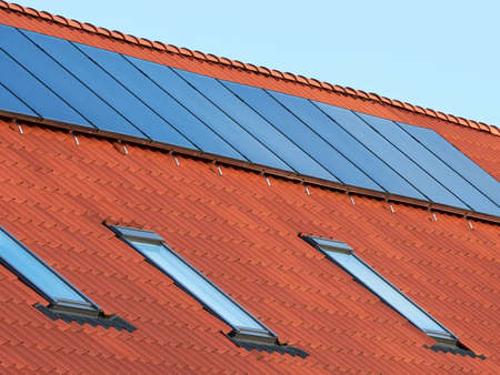 solar thermal: Flat plate solar thermal collectors on a red tile roof