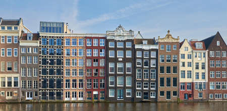 canal houses: Amsterdam, Netherlands – March 10, 2016: Canal houses in Amsterdam, with blue skies in the background Editorial