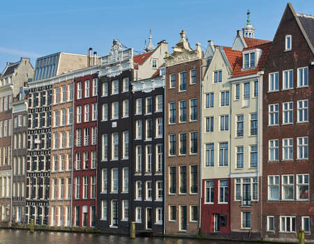 canal houses: Amsterdam, Netherlands – March 10, 2016: Canal houses in Amsterdam, with blue skies in the background
