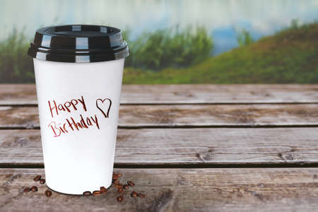 Happy Birthday coffee to-go cup on a rustic wooden table. Nature background and wallpaper. Easy to customize.
