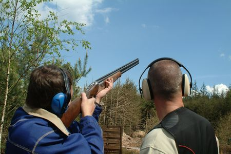 traps: Man shooting clay pigeons being instructed Stock Photo