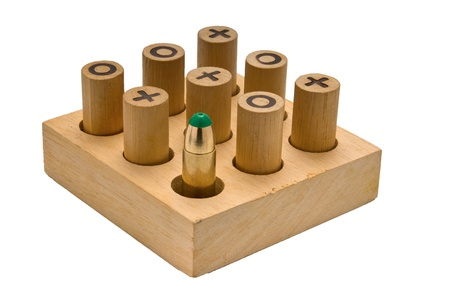 Wooden Tic Tac Toe game with one bullet hinting at the senseles war games photo