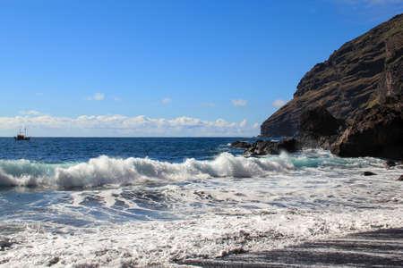 Black sand and sailing boat at the beach Playa La Veta Фото со стока
