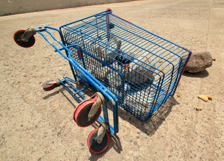 shopping cart with full of rocks in the water channel Stock fotó