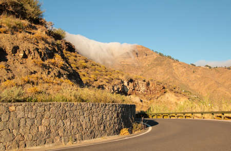 the clouds are swashing over the hills on gran canaria 版權商用圖片