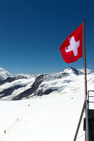 Swiss flag on top of mountains covered in snow photo