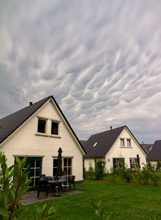 Mammatocumulus clouds above bungalow houses