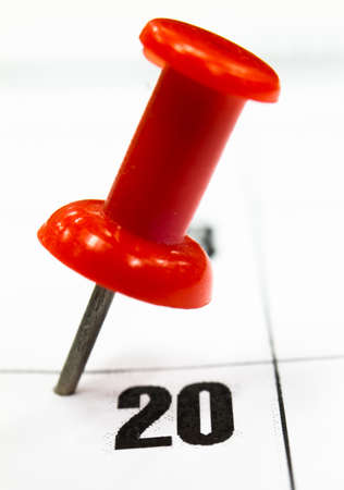 up date: Close up push pin selecting a date on the calendar