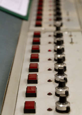 A row of buttons and switches on an old control panel photo